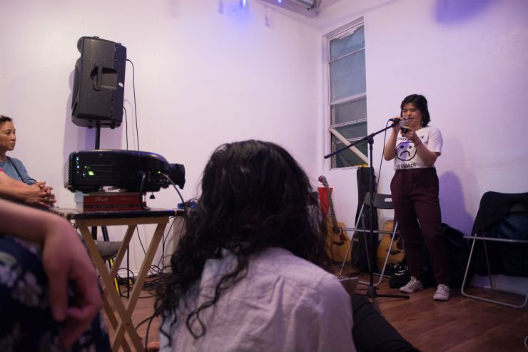Rachel reads to an audience from her phone in white shirt and maroon pants