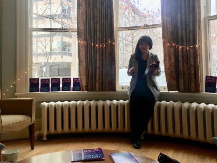 Rachel reads from the UC Review in black clothes and a blazer, in front of windows