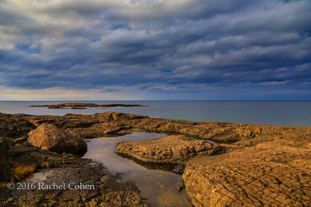 """""""Rocky Stormin"""" Sunlight and storm clouds on the rocky shores of Presque Isle Park in Marquette, Michigan."""