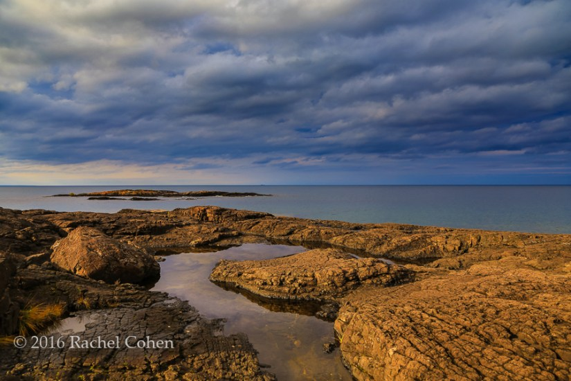 """Rocky Stormin"" Sunlight and storm clouds on the rocky shores of Presque Isle Park in Marquette, Michigan."