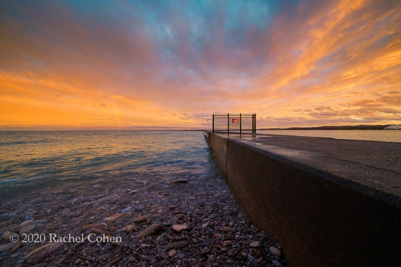 """Breakwater Skies 2""  Amazing clouds and colors of sunset along the rocky beach at Marquette Breakwater!"