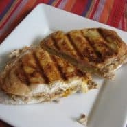 Cuban panini sliced in half on a square white plate.