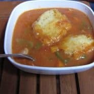 Cornmeal dumplings in a tomato based chicken stew, in a white bowl.