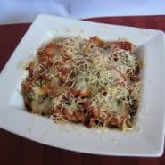 Baked pasta in a square white bowl covered with cheese.