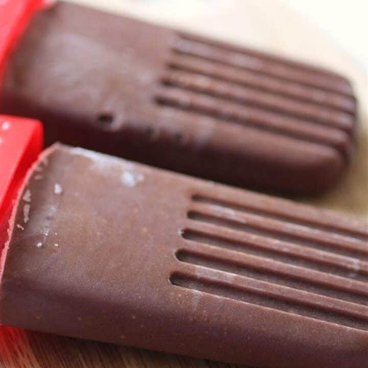 Two chocolate pudding pops on a wooden board.