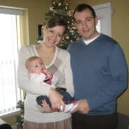 A young couple, standing and holding their baby in front of a Christmas tree.