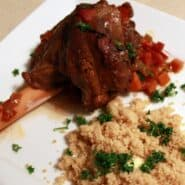 Close up image of one lamb shank on white plate with couscous, parsley sprinkled on top.