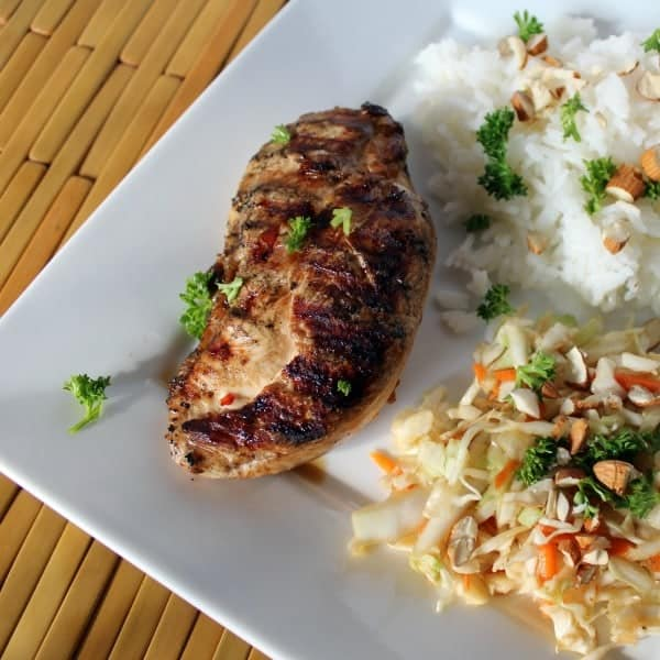 Overhead view of a grilled chicken breast with Asian style coleslaw, and rice.