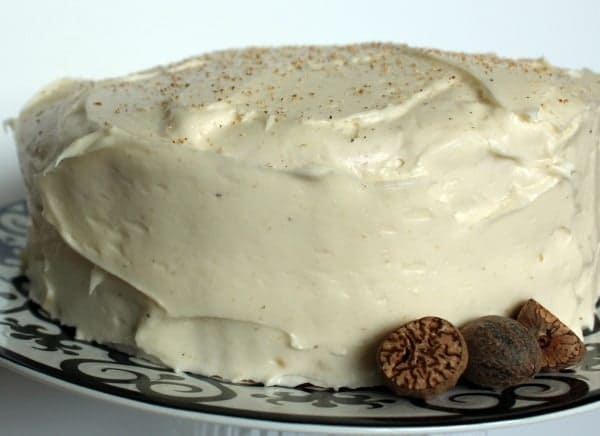 Front view of whole layer cake on white platter with black pattern, garnished by whole nutmeg.