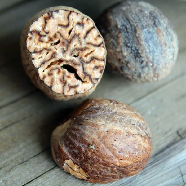 Close up Image of one whole nutmeg, and one sliced in half, showing the inside. Background is wooden deck.