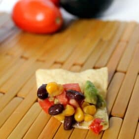Black beans, corn, tomato, and avocado on a chip.