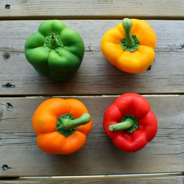 Four bell peppers on a wooden background; one green, one yellow, one red, one orange. Viewed from above.