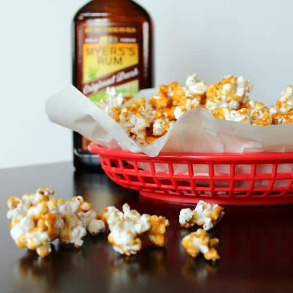 Caramel corn in paper lined red basket, with some on table in front of bowl, A bottle of Myers's rum in background.