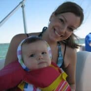 A woman with a baby on a boat, the baby is wearing a life vest.