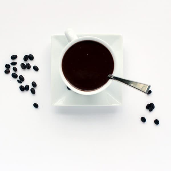 Overhead view of white coffee cup on square saucer, containing mocha hot fudge and a spoon. Several coffee beans are scattered on the white background.