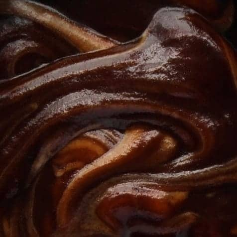 A very close up view of fudge sauce, showing the swirls of peanut butter.