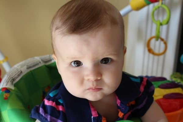 Close up image of same child, sitting in a child seat, looking at camera with serious expression.