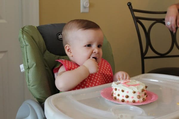 One year old eating cake on her birthday.