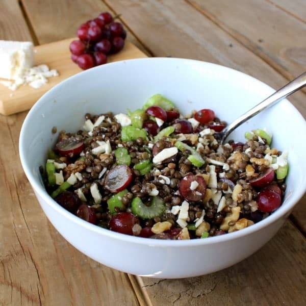 A large white bowl full of a lentil salad with lentils, celery, feta, grapes, and walnuts. Grapes and feta are also pictured in the background.
