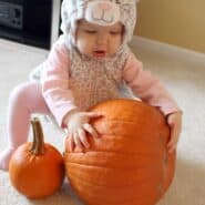 Cute baby girl in a cat costume with a pumpkin.