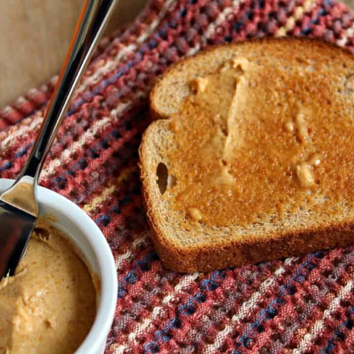 A small white bowl filled with a compound butter made with pumpkin. Also pictured are a slice of toast and a knife/spreader.