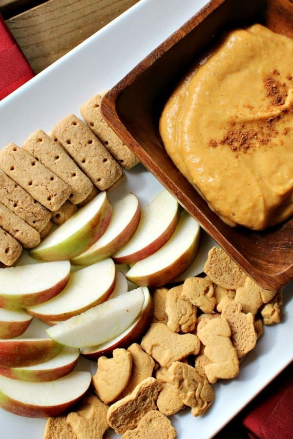 Overhead view of a pale orange dip in a wooden bowl, on a white plate with graham cracker sticks, animal crackers, and sliced apples.