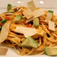 Messy pile of pasta with avocado chunks and crispy tortilla strips.
