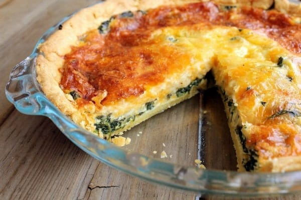 Image of a spinach quiche in a glass pan with one slice removed.