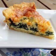 Image of a slice of spinach quiche on a white plate.