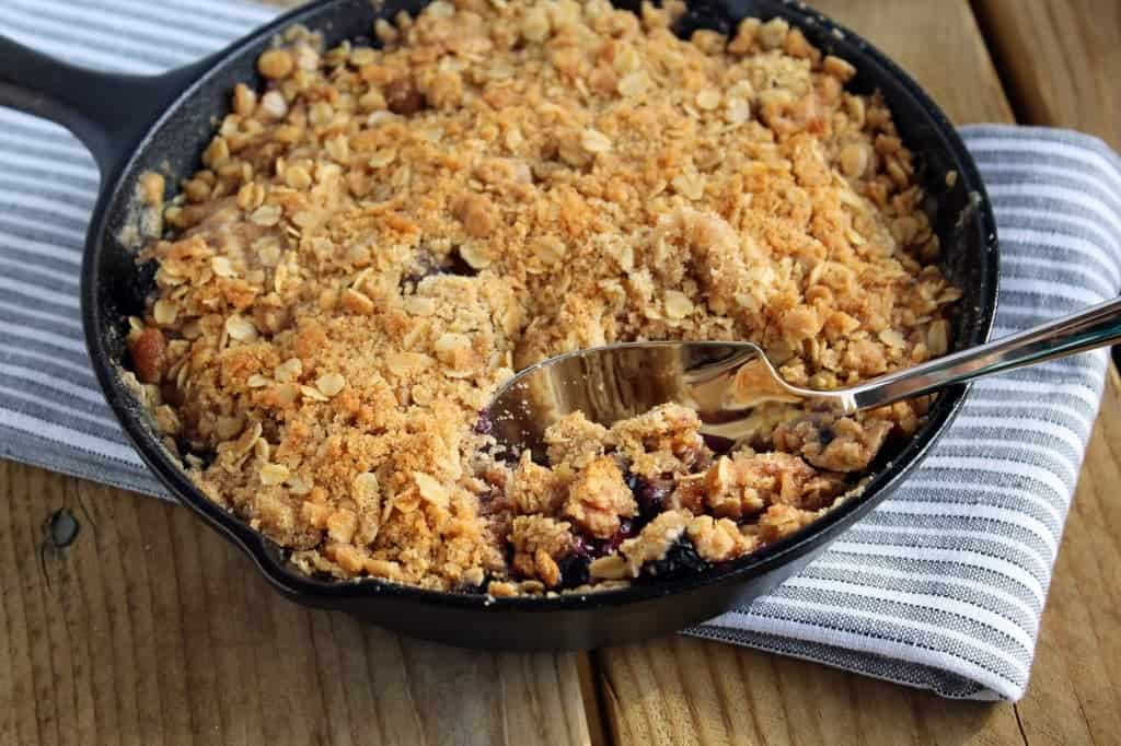 This apple blueberry crisp recipe is served in an adorable cast iron pan - it's the perfect dessert for any occasion and one of our absolute favorites!