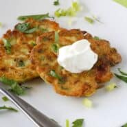 Two zucchini and feta pancakes on a white plate, garnished with sour cream and sliced scallions.
