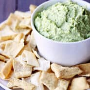 Closeup view of light green dip in a white bowl, surrounded by pita chips.