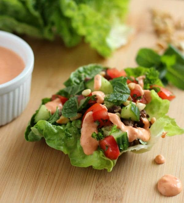 Lamb lettuce wraps with a red pepper hummus sauce - a healthy, filling, and flavor-packed meal! Get the easy and healthy meal on RachelCooks.com!