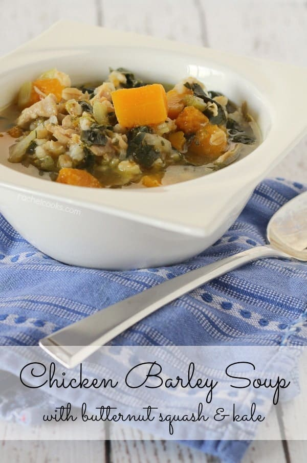 "Front view of chicken barley soup in white bowl, with spoon along side, on a blue patterned cloth. Text overlay reads ""Chicken barley soup with butternut squash & kale."""