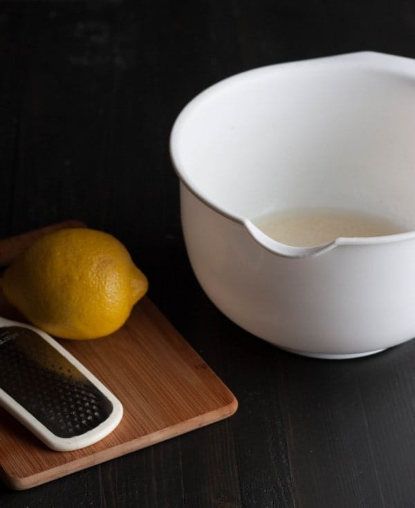 Image consists of partially shown white mixing bowl, cutting board, whole lemon, and zester, on a black background.