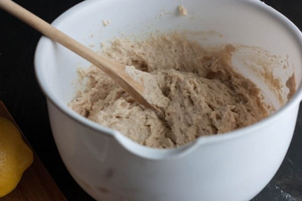 Closeup of mixing bowl containing cake batter and wooden spoon.