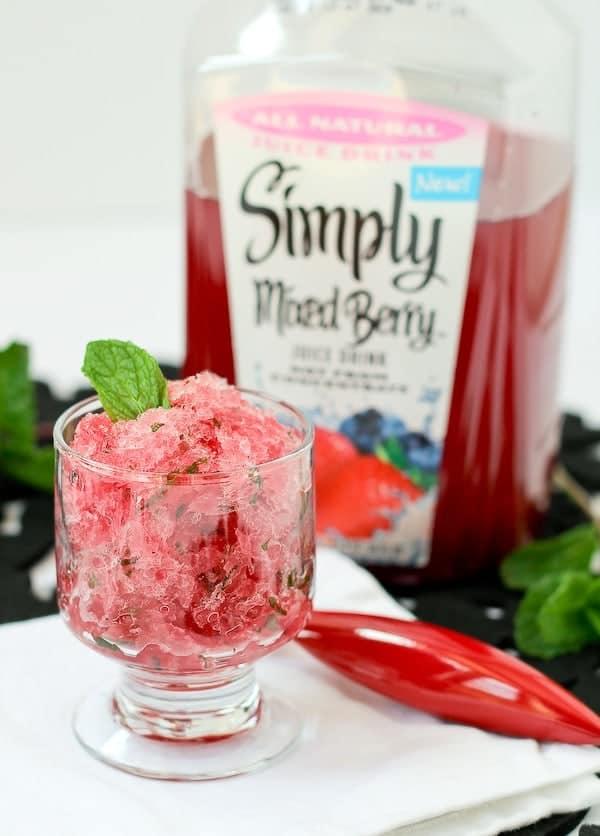 图像由右脚透明玻璃甜点菜与冰冷的红色格兰尼,单薄荷叶伪装的。简单地混合浆果果汁的塑料瓶是在后台。