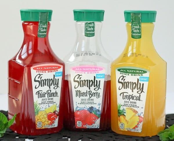 果汁饮料,混合浆果和热带:3瓶只需果汁的形象。混合浆果瓶是半空。