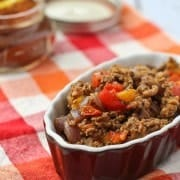 Taco meat in a brown oval bowl.