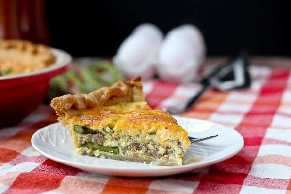 Slice of turkey sausage and asparagus quiche on a round white plate.