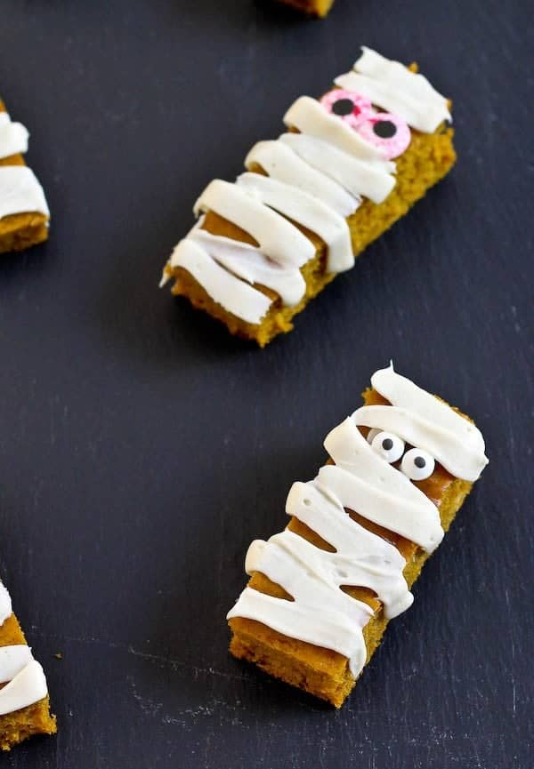 Don't throw a Halloween party without these fun pumpkin bar edible mummies. They use a lessened amount of sugar and are low in fat so you can maybe even eat two mummies! Get the easy recipe on RachelCooks.com!
