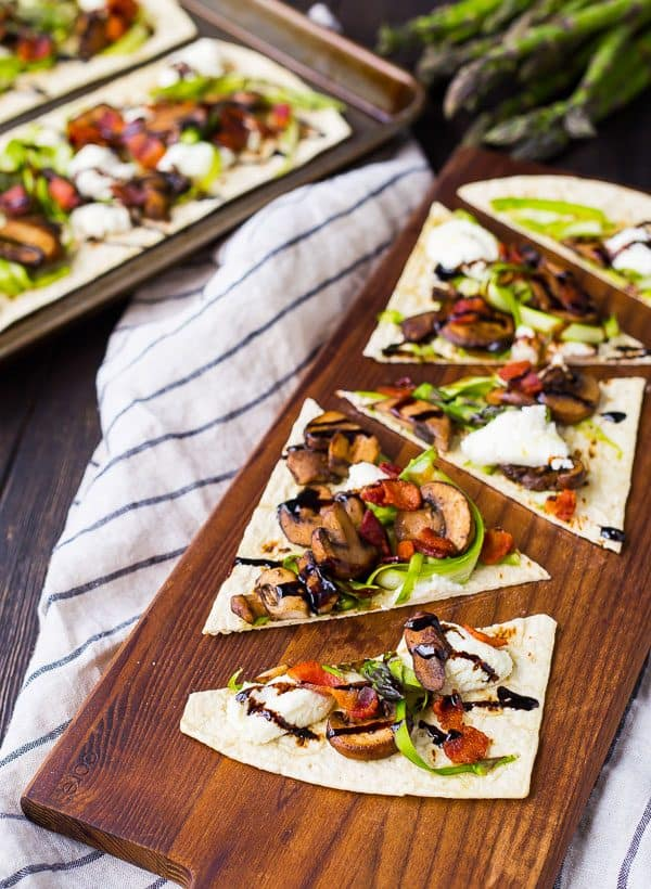 Coming together in less than 10 minutes, this mushroom flatbread with bacon, ricotta, and shaved asparagus is the perfect quick and easy summer lunch or dinner. You'll love the contrast of fresh and rich flavors! Get the recipe on RachelCooks.com!