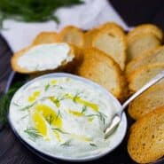 Whipped feta with lemon and dill is the perfect summer spread! Classy and sophisticated with the bright flavors of lemon, it's perfect spread on a crisp slice of French bread! Get the easy recipe on RachelCooks.com!