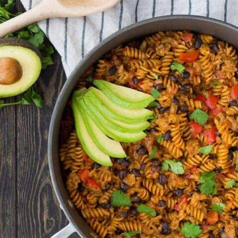 In a rush? This 30 minute One Pot Taco Pasta with Ground Turkey and Black Beans is here to save the day! It's creamy, satisfying, and the pasta cooks in the same pan as everything else! Get the healthy 30 minute recipe on RachelCooks.com!