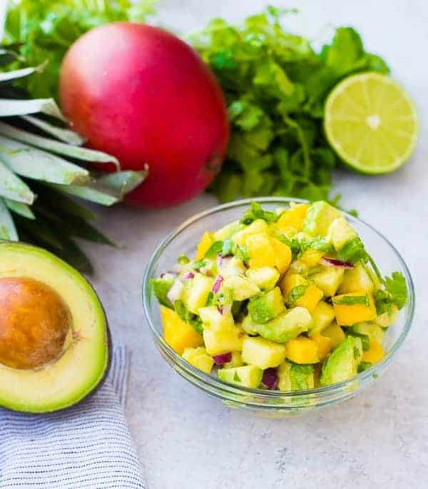 Mango Avocado Salsa is the perfect topping to any taco or salad, and it's irresistible piled up on a chip! You'll love the creamy avocado, sweet mango, and tart pineapple in every bite! Get the easy salsa recipe on RachelCooks.com!