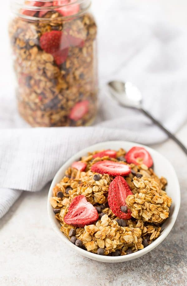 chocolate chip granola in bowl with jar in background