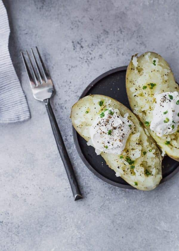 image of baked potato cut in half with sour cream and chives