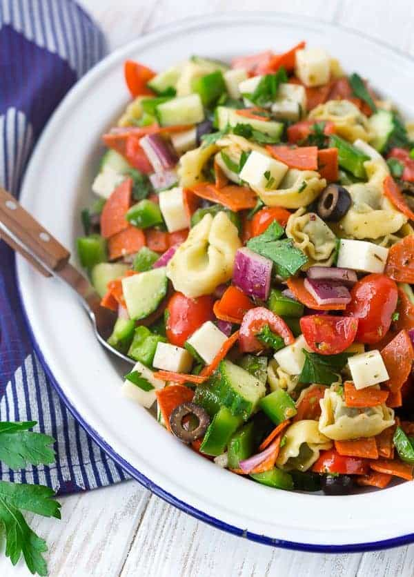 Image of tortellini pasta salad on a white plate with wooden spoon