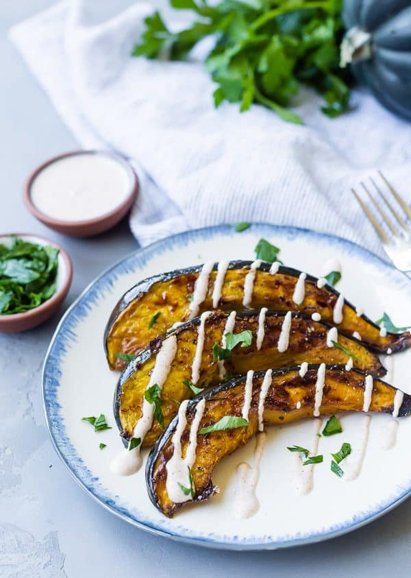 Blue-rimmed white plate with three slices of roasted acorn squash, with a drizzle of white sauce.