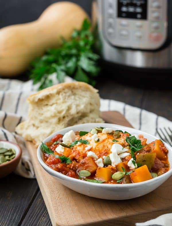 Small bowl of tomatoes, eggs, feta cheese, and pepitas. An instant pot is pictured in the background.